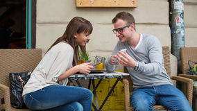 Pares jovenes con la tableta en café. Imagen de archivo