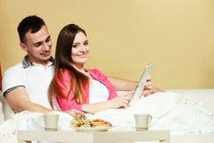 Pares jovenes con la tableta y la tarjeta de crédito en casa Foto de archivo