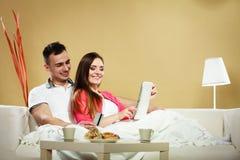 Pares jovenes con la tableta y la tarjeta de crédito en casa Foto de archivo libre de regalías