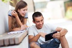 Pares jovenes con la tablilla digital Foto de archivo libre de regalías