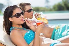 Pares jovenes con las bebidas por la piscina Foto de archivo libre de regalías