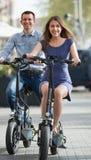 Pares jovenes con las bicis eléctricas imágenes de archivo libres de regalías