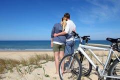 Pares jovenes con las bicis que abrazan en la playa Imagen de archivo