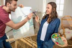 Pares jovenes con las brochas que se divierten mientras que pinta junto Fotografía de archivo