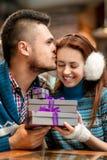 Pares jovenes con las cajas de regalo en el café en invierno Fotografía de archivo libre de regalías