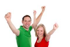 Pares jovenes con las manos con los brazos para arriba Imagen de archivo libre de regalías