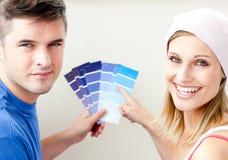 Pares jovenes con las muestras del color para el sitio de la pintura Imágenes de archivo libres de regalías