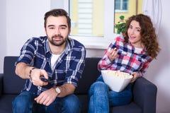 Pares jovenes con las palomitas que miran la TV o la película Fotos de archivo