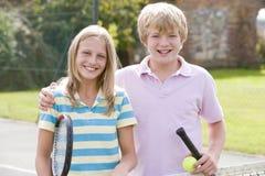 Pares jovenes con las raquetas en la sonrisa del campo de tenis Fotos de archivo libres de regalías