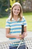 Pares jovenes con las raquetas en la sonrisa del campo de tenis Foto de archivo