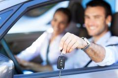 Pares jovenes con llaves al nuevo coche Imagen de archivo