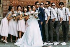 Pares jovenes con los amigos divertidos en la boda imagenes de archivo