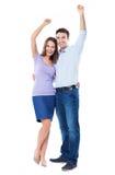 Pares jovenes con los brazos aumentados Foto de archivo libre de regalías