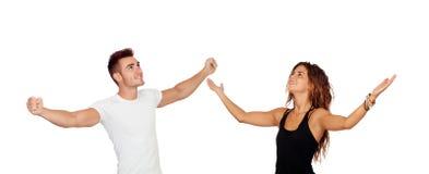 Pares jovenes con los brazos aumentados celebrando algo Imagen de archivo