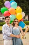 Pares jovenes con los globos Imágenes de archivo libres de regalías