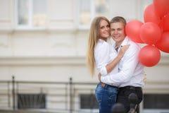 Pares jovenes con los globos coloridos en ciudad imagen de archivo