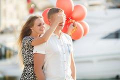 Pares jovenes con los globos coloridos en ciudad imagenes de archivo