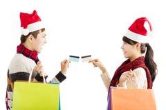 Pares jovenes con los panieres y tarjeta de crédito para la Navidad Fotos de archivo libres de regalías