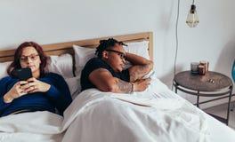 Pares jovenes con los teléfonos elegantes en su cama fotografía de archivo
