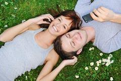 Pares jovenes con los teléfonos móviles Imagen de archivo libre de regalías