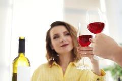 Pares jovenes con los vidrios de vino delicioso dentro fotos de archivo