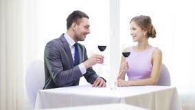 Pares jovenes con los vidrios de vino en el restaurante almacen de metraje de vídeo