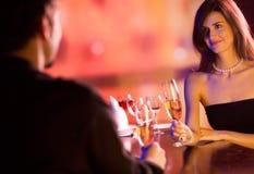 Pares jovenes con los vidrios del champán en restaurante Fotografía de archivo