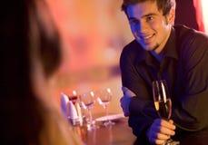 Pares jovenes con los vidrios del champán en restaurante Fotos de archivo libres de regalías
