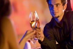 Pares jovenes con los vidrios del champán en restaurante Imagen de archivo libre de regalías
