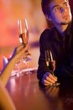 Pares jovenes con los vidrios del champán en restaurante Fotografía de archivo libre de regalías