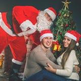 Pares jovenes con Papá Noel que celebra el Año Nuevo 2017, la Navidad Imagenes de archivo