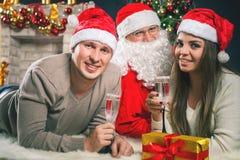 Pares jovenes con Papá Noel que celebra el Año Nuevo 2017, la Navidad Foto de archivo libre de regalías