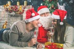 Pares jovenes con Papá Noel que celebra el Año Nuevo 2017, la Navidad Imágenes de archivo libres de regalías