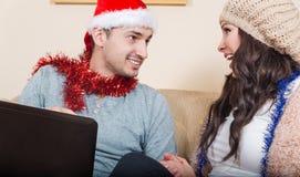 Pares jovenes con Santa Hat roja, sentándose en el sofá Fotografía de archivo libre de regalías