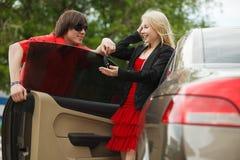 Pares jovenes con un coche Imagen de archivo