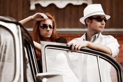 Pares jovenes con un coche retro. imágenes de archivo libres de regalías