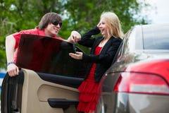 Pares jovenes con un nuevo coche. Fotografía de archivo libre de regalías