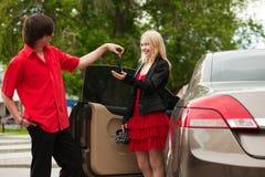 Pares jovenes con un nuevo coche. Foto de archivo libre de regalías