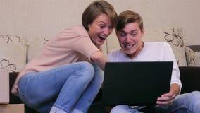 Pares jovenes con un ordenador portátil en un piso metrajes