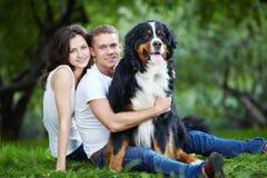 Pares jovenes con un perro imagen de archivo libre de regalías