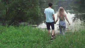 Pares jovenes con un perro en el banco del lago almacen de video