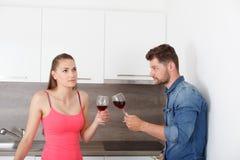 Pares jovenes con un vidrio de vino rojo fotos de archivo libres de regalías