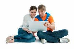 Pares jovenes con una computadora portátil Imagen de archivo