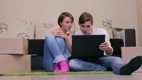 Pares jovenes con una computadora portátil metrajes
