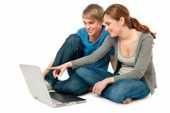 Pares jovenes con una computadora portátil Imágenes de archivo libres de regalías