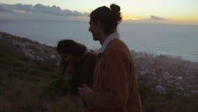 Pares jovenes de amor en el acantilado en la puesta del sol almacen de video