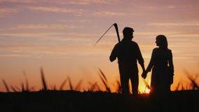 Pares jovenes de granjeros en el campo, disfrutando de la puesta del sol Inicio en el concepto del negocio agrícola foto de archivo libre de regalías