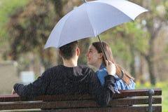 Pares jovenes de Heppy que se sientan en banco en el día de primavera lluvioso Fotos de archivo libres de regalías