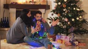 Pares jovenes de la alegría linda que se sientan en el árbol de navidad en el piso en el cuarto La mujer que da la caja de regalo almacen de video