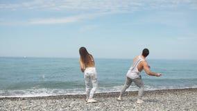 Pares jovenes de la aptitud que abrazan la colocación en la playa, mirando horizonte metrajes